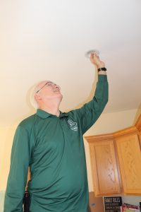 HWE installing an LED lightbulb during a home energy assessment